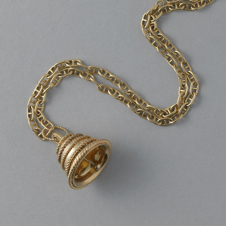 An 18 carat gold pendant of a functioning bell decorated with five horizontal stripes of twisted gold wire, signed and numebered: Van Cleef & Arpels, NY, 10 V 17249.  Chain is not VCA and is sold separately.  weight: 20.21 grams dimensions: 3.5 x