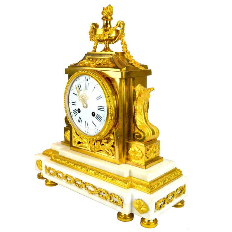 A very finely cast Louis XVI style marble and gilt bronze clock of architectural form. The rectangular stepped white marble bases sitting on six toupie feet, the lower front frieze decorated with paterae and entwined gilded floral vines. The white