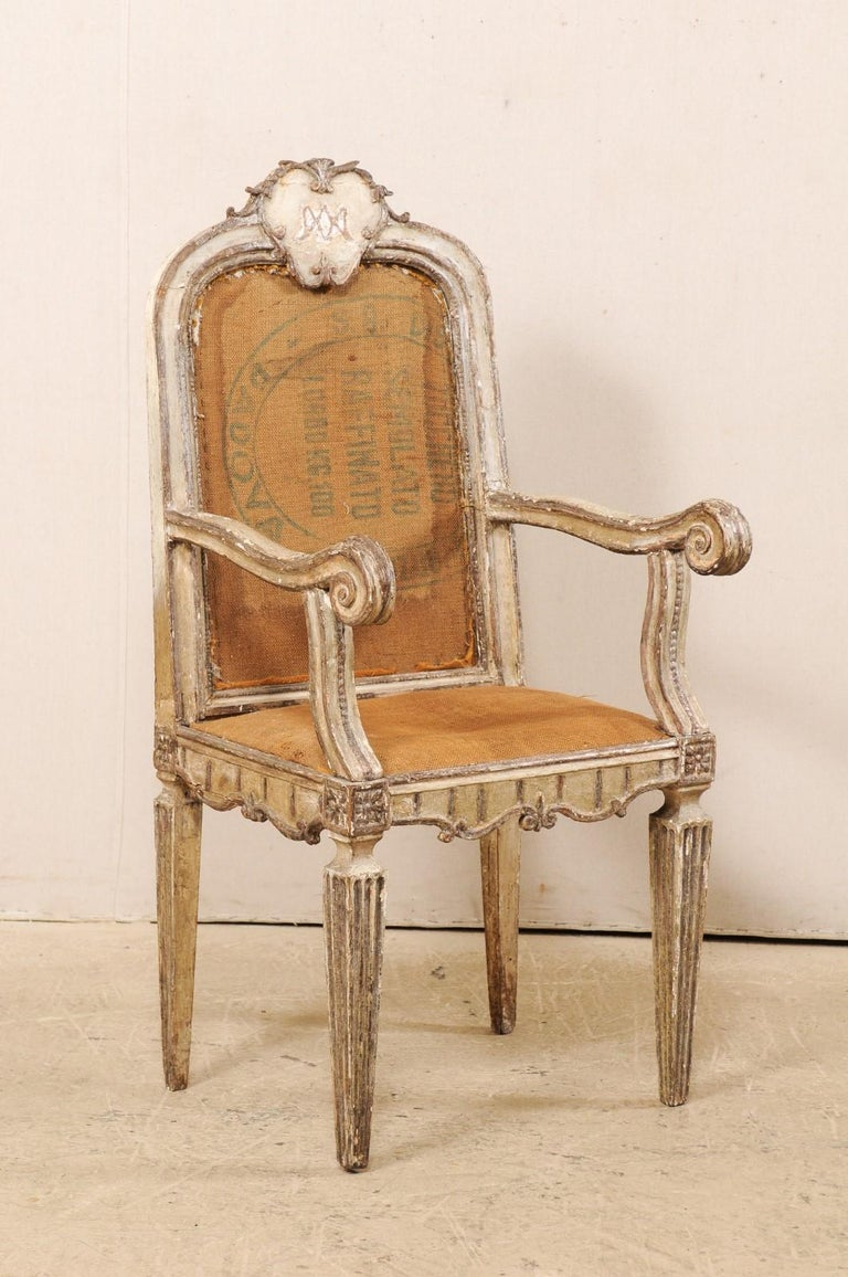 A single Italian carved-wood accent armchair from the 18th century. This antique chair from Italy has a nicely carved stylized plaque adorning its back rail crest. Gently curved arms terminate into scrolled knuckles. The seat and arch-shaped back