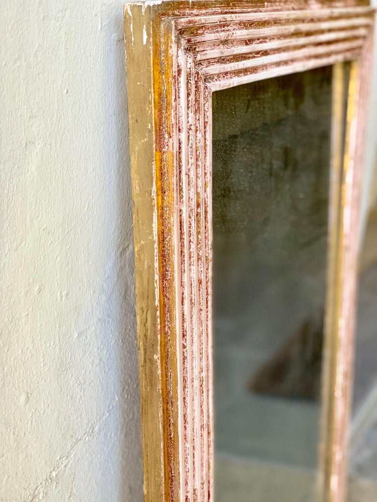 An early 18th century French mirror with some original gilded accenting. The frame is carved, highlighting the gilding and the mercury glass.