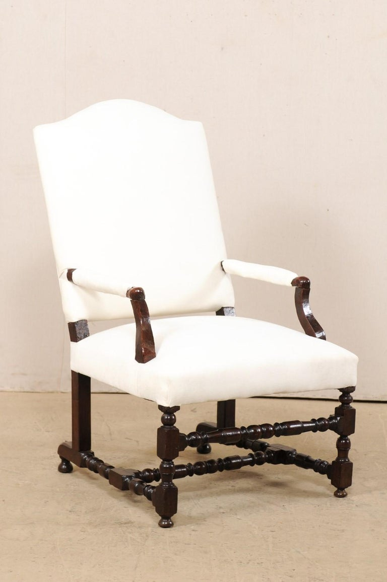 An Italian carved wood armchair from the 18th century with new upholstery. This antique chair from Italy has a large camel-back which is set at a comfortably reclined position, with upholstered seat, back, and arm rests. The chair is raise on nicely
