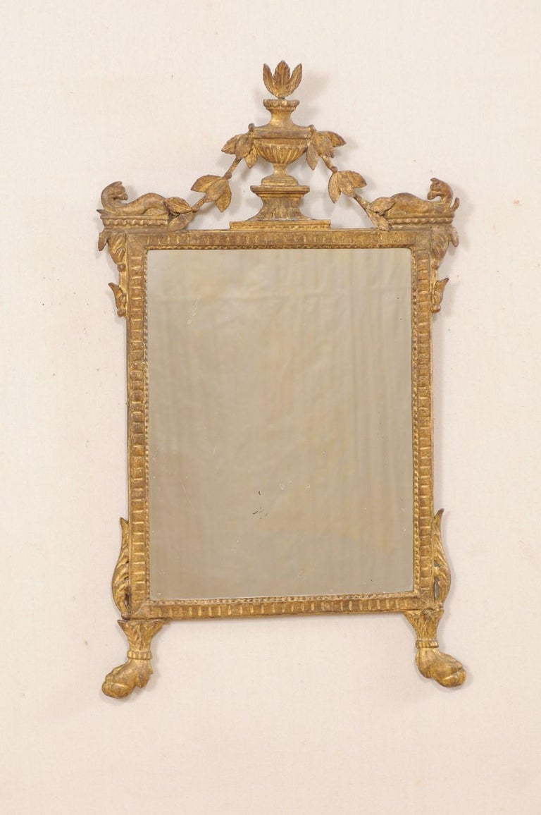 An Italian neoclassical carved and giltwood mirror from the 18th century. This antique mirror from Italy features a richly carved giltwood surround, in typical neoclassical style, adorn with a raised urn crest at top center of frame, with various