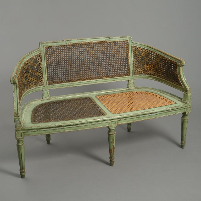 A late 18th century painted canapé sofa in the neoclassical taste, the green painted channeled frame with caned back and seat panels and raised upon turned tapering fluted legs. Having a drop in seat.