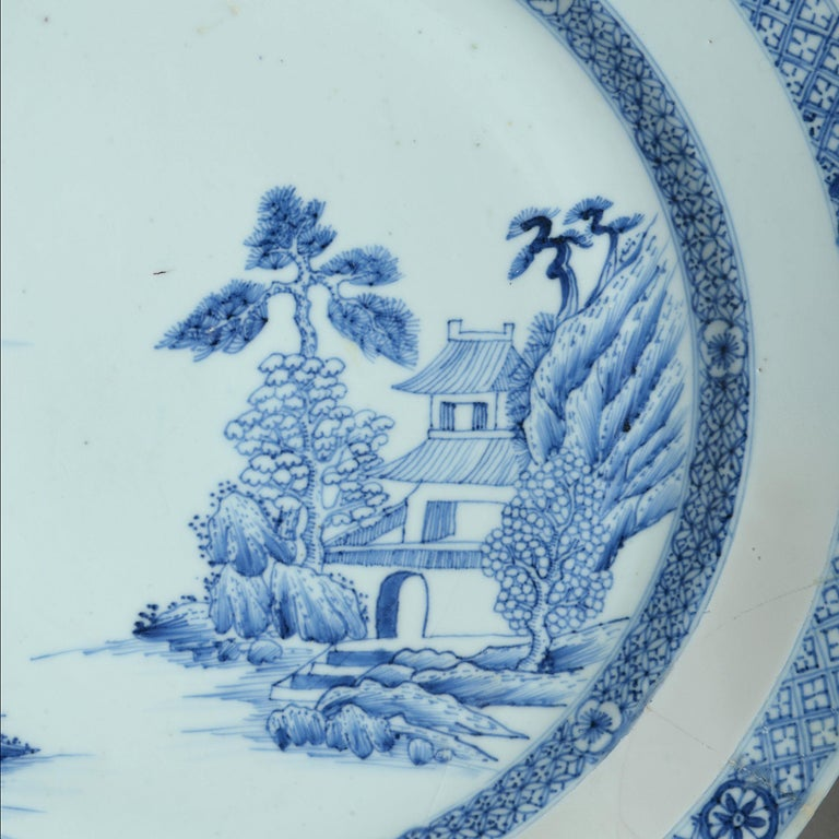An 18th century blue and white porcelain charger, decorated with an imaginary landscape and foliate borders.