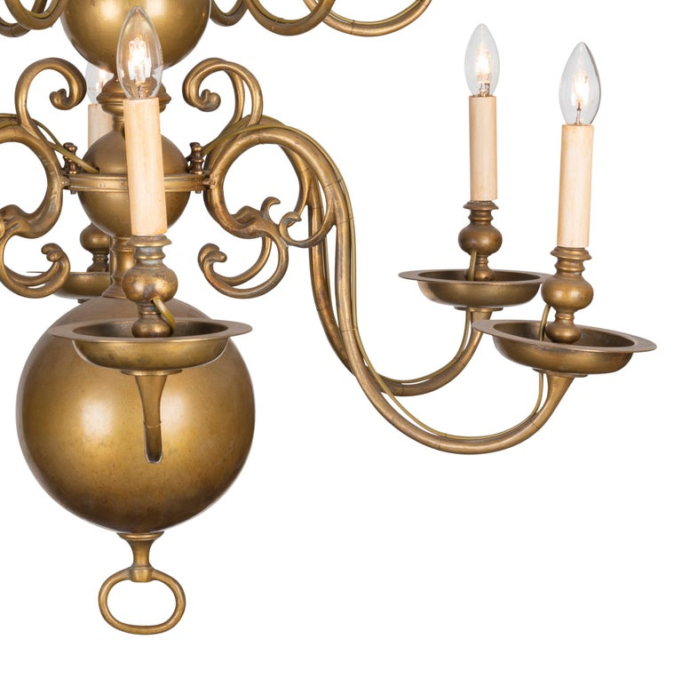 The graduated globular baluster stem with two graduated tiers, each tier with six scroll arms to drip pans and bud nozzle with faux candle lights to ring finial. Electrified.