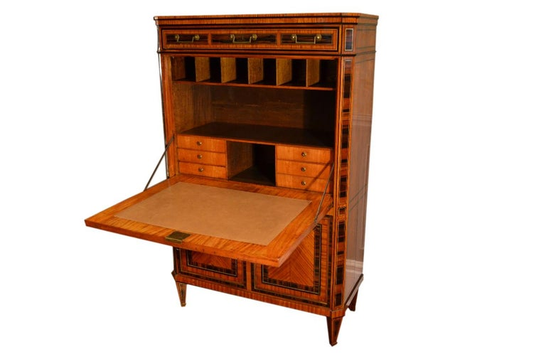 A late 18th century Dutch satinwood abbatant or drop front desk, with gilded beading and inlaid brass stringing. The case also has various exotic woods inlaid into the satinwood. There is a drawer in the frieze above a fall-front door enclosing a