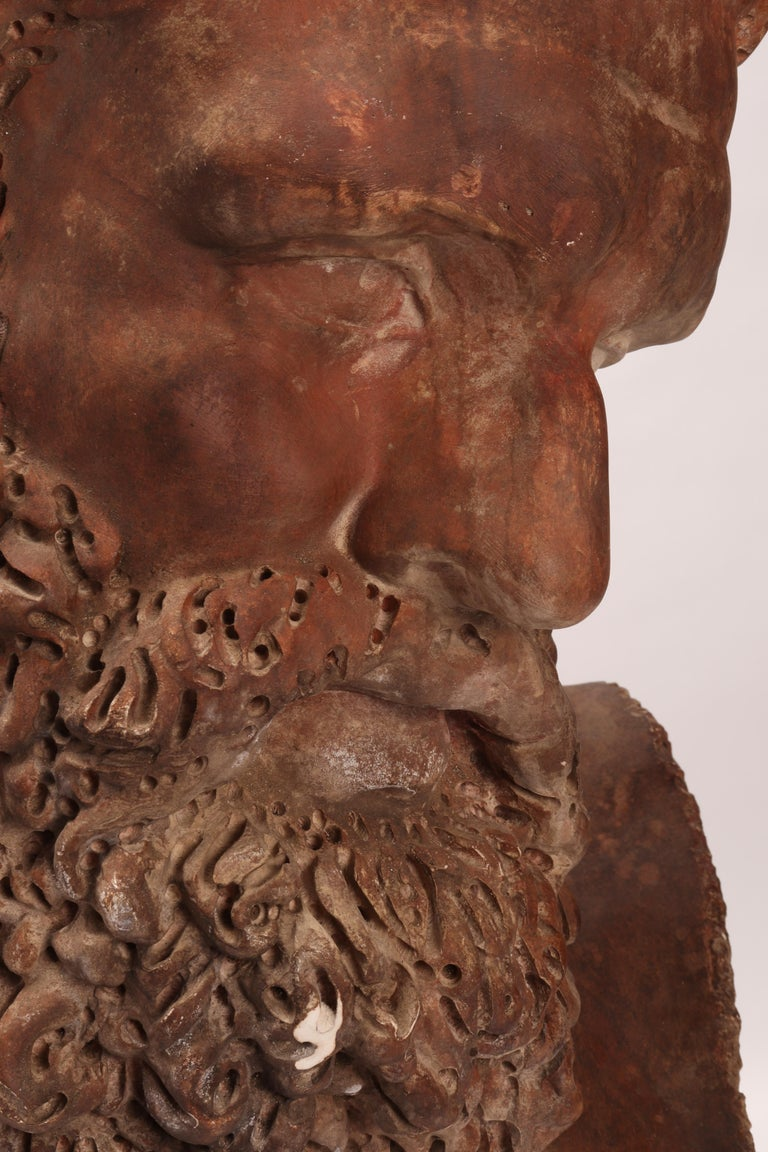 Over the wooden black painted base is set the cast of a big Hercules head. Patina like a terracotta. The cast for drawing teaching in Academy, Italy, circa 1880.
