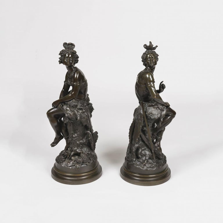 An African couple by Frédérick Eugène Piat (1827-1903)  Modelled in a now well patinated bronze, the circular bases, inscribed with the artist's name, support tree trunks, against which rest the young warrior holding his spear, and his partner, a