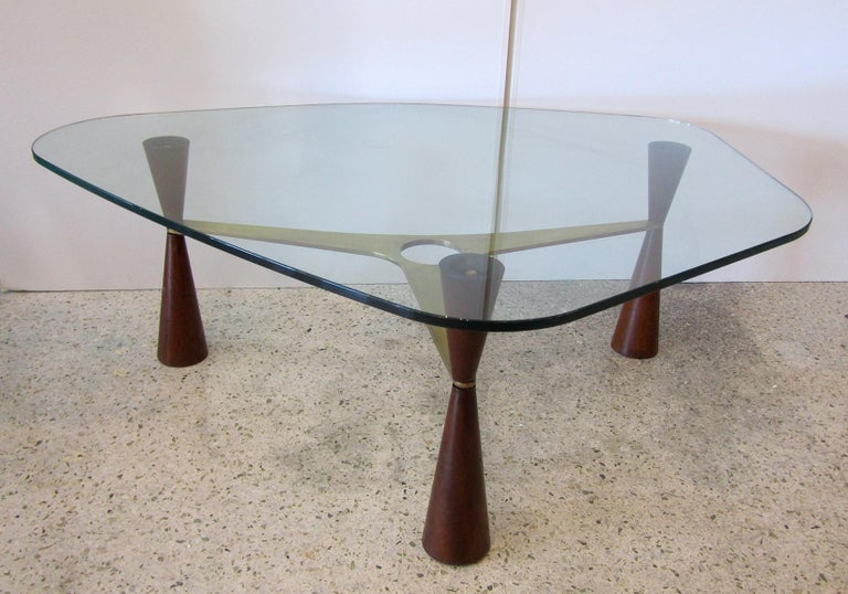 A beautiful and unusual coffee table by Ed Wormley for Dunbar. A freeform glass top sits on top of 3 tapering legs divided by a brass stretcher with a circular cutout. There is beautiful brass hardware throughout the piece. Dimensions of base alone: