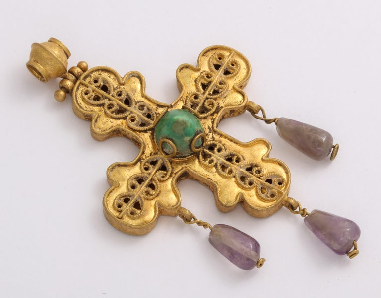 Made from the fine jewelers of the Byzantine period, known for their quality, this magnificent openwork cross suspends three teardrop amethyst stones and is centered with a conical  emerald.  Enlarge the images and take in the openwork that is