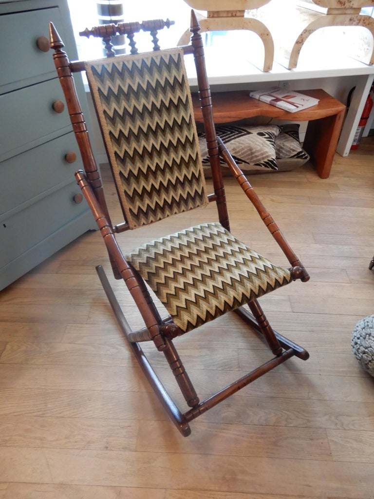 A charming little rocker with all the bells and whistles of the George Hunzinger style. Handcrafted and upholstered in a modern woven beige and green top grade fabric. Excellent condition.
