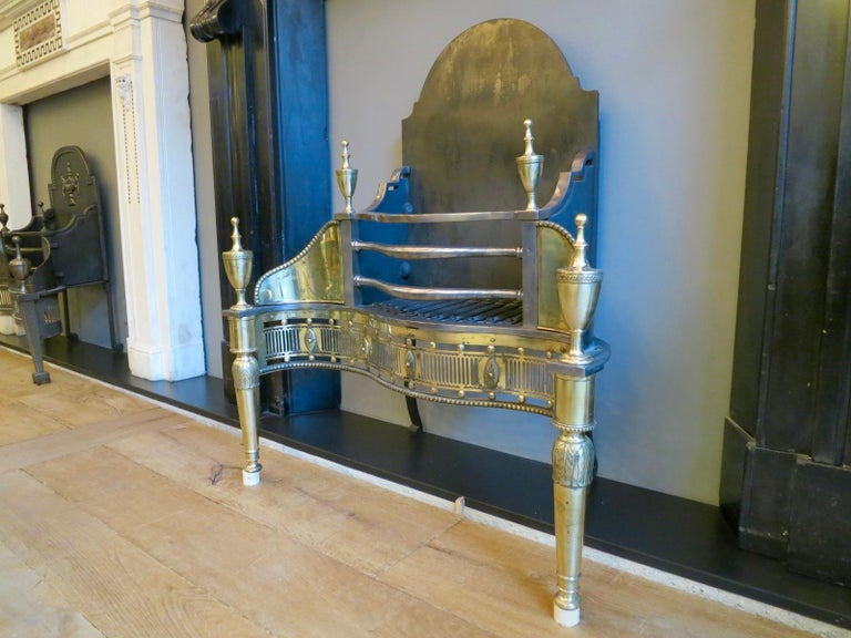 A 19th century fire grate with tapering front supports with acanthus detail and surmounted by classical urn finials. The wings engraved with tied ribbons, bell drops and oval patarae, flanking a bowed bar burning area, above a serpentine pierced