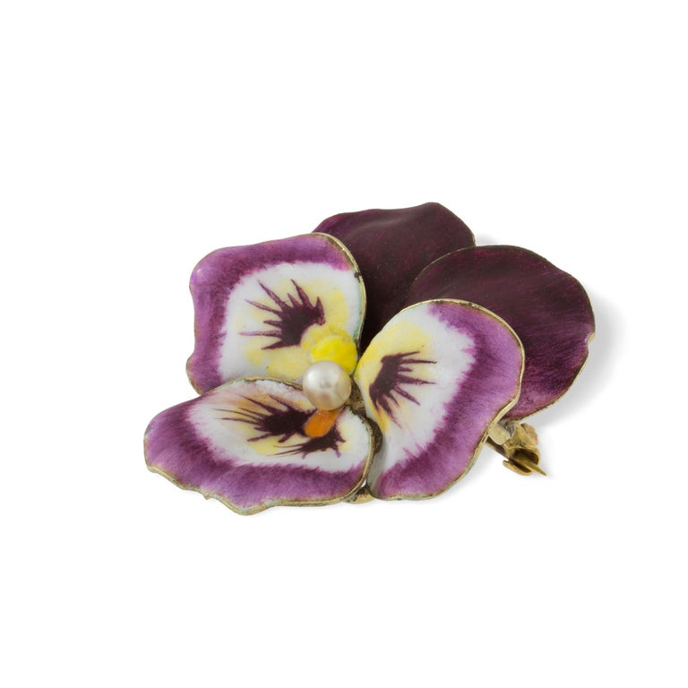 An antique enamel and pearl pansy brooch, the round pearl measuring approximately 3mm set to the centre of five realistically carved and enamelled petals with a yellow gold back with brooch fittings,  circa 1900, made by A.J Hedges & Co in the USA,