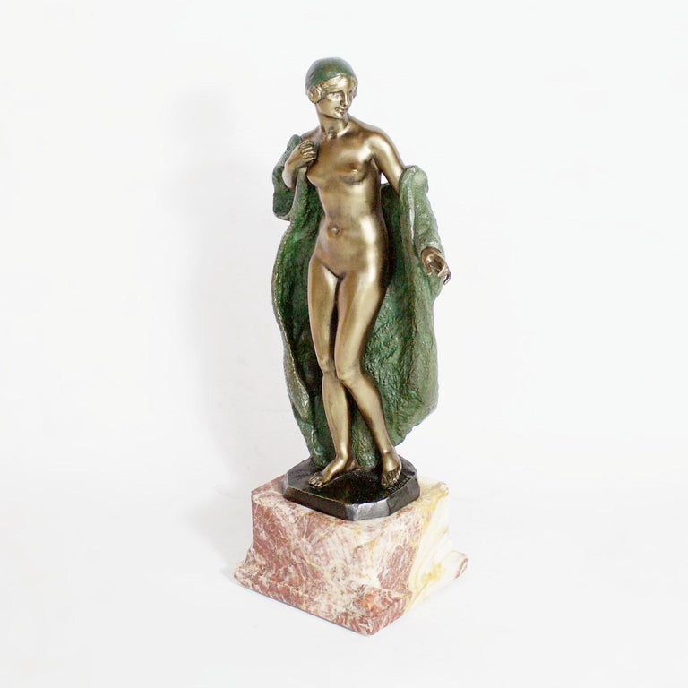 An Art Deco bronze sculpture by Joé Descomps of a nude female wearing a loose green patinated cloak and matching colored head scarf. Signed 'Joé Descomps' to bronze. Set over a variegated marble base.  Artist: Joé Descomps