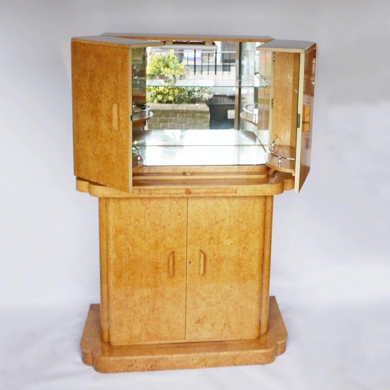 An Art Deco cocktail cabinet by Harry & Lou Epstein. Bleached burr walnut veneered on solid walnut and mahogany. Upper mirrored lit section with glass shelf. Mirrored pull out tray with original amber bakelite handle. Lower section opens to bottle