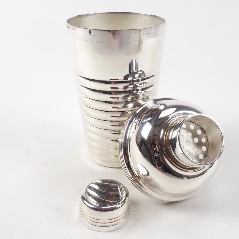 An Art Deco cocktail shaker of stylish curves and lobed horizontal ribs. The fluid lines and bold modernist design are indicative of the chic elegance of the era.