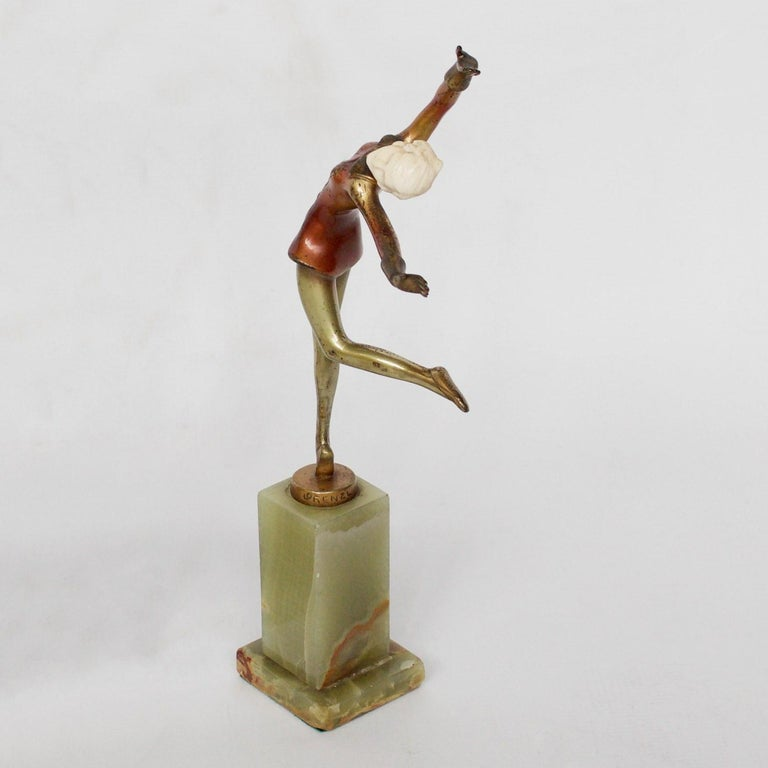 An Art Deco, cold painted bronze figure of an elegant dancer dressed in a buttoned red jacket, arms out stretched in an extravagant pose. Hand carved ivory head, raised on a green onyx base. Original enamel patination.   Signed Lorenzl to