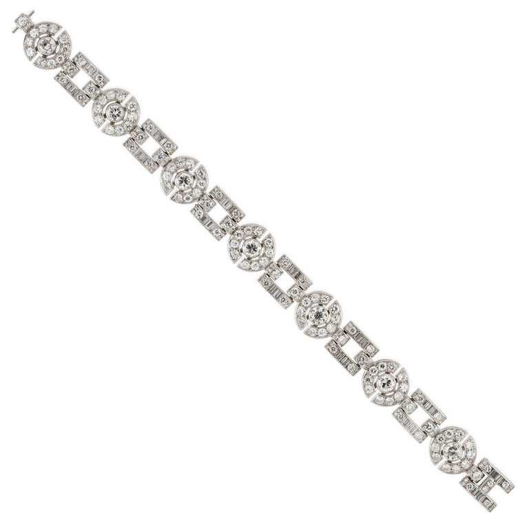 An Art Deco diamond bracelet, consisting of seven old European-cut diamonds, rubover-set within circular-shaped openwork links encrusted with smaller old European and swiss cut diamonds, alternating with square shaped openwork links set with