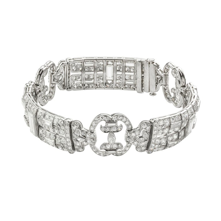 An Art Deco flexible diamond-set bracelet, the three rectangular openwork panels, each centrally-set with a baguette-cut diamond, connected with three open links of scroll design, set throughout with old brilliant, baguette, marquise and swiss-cut