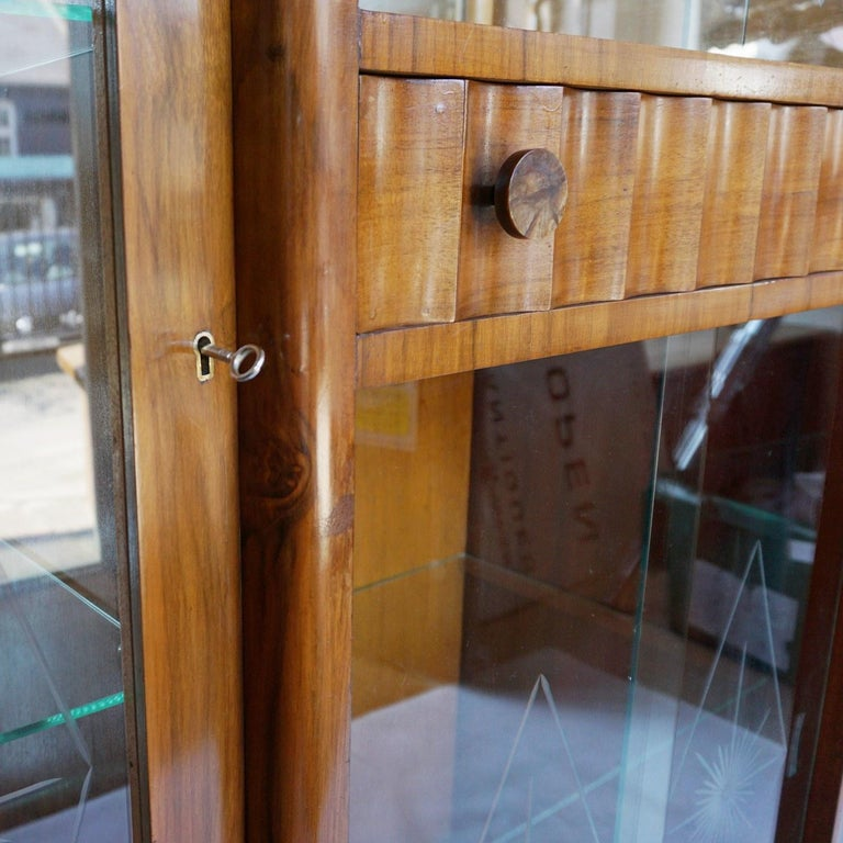 An Art Deco display cabinet. Central shelved glass fronted section below a curved walnut drawer with bakelite handles. Flanked on either side by glass shelved display cabinets visible from both front and side. Original patinated glass. Burr and