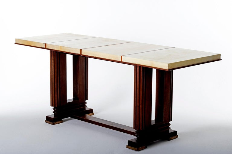 An Art Deco mahogany and velum console table, by Gauthier-Poinsignon, of very generous proportions. The base with bronze feet, of geometrically stylized lyre shape, supporting a top of for sections covered in velum France, circa 1925.