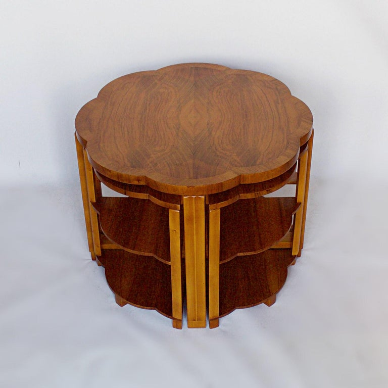An Art Deco nest of tables by Harry & Lou Epstein. Burr walnut veneered, cloud shaped tabletop, with straight grain walnut banding and figured walnut legs. Four pullout / pull-out side table nests.  Dimensions: Table, H 56cm, W/D 74cm side tables,