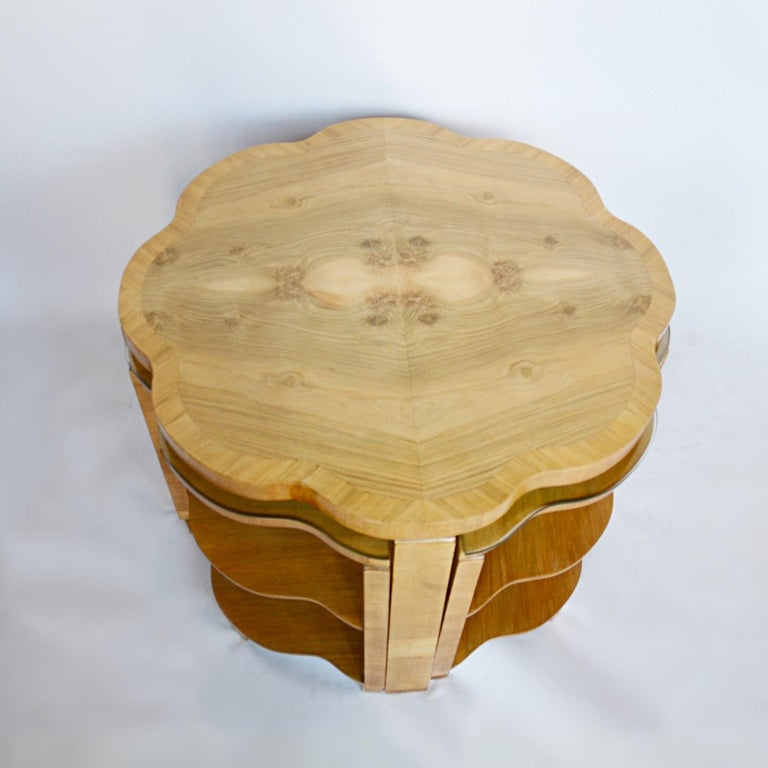 An Art Deco nest of tables by Harry & Lou Epstein. Burr walnut veneered cloud form table top with straight grain walnut banding. Four matching cloud form, straight grain walnut veneered pull out nests  Dimensions: H 55cm W 76cm D 76cm Nests: H