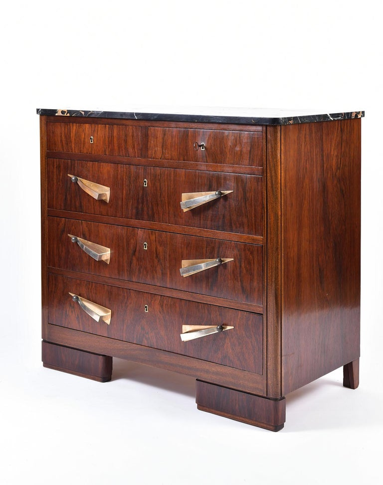 An Art Deco rosewood and Portoro marble-top chest of drawers, the five drawers with brass and nickel plate brass handles and brass key holes, with a key in working order, on rounded rectangular feet. France, circa 1930.