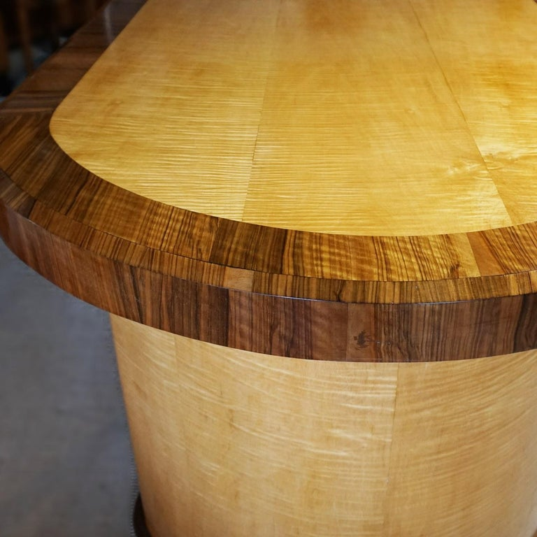 An Art Deco table with Satin Birch veneers and figured walnut banding. tabletop sits over two crescent shaped pedestals linked by a Satin Birch and walnut veneered stretcher. Veneered all round. This table can be used as a dining table, centre table