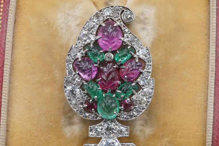 An Art Deco Tutti Frutti platinum and diamond brooch by Cartier features emerald, ruby for green and red motifs. Signed  'Cartier Paris'.  Tutti Frutti creations are emblematic of the Cartier style, a result of the meeting between creativity and