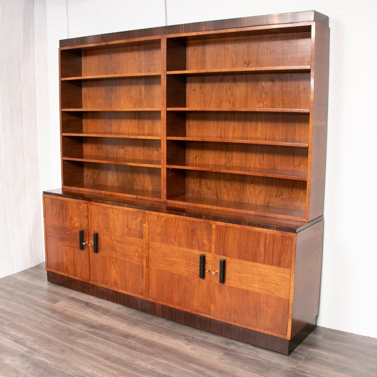 An Art Deco bookcase with open top and cupboard base enclosing shelves featuring crossbanding throughout and ebonized handles, circa 1930.