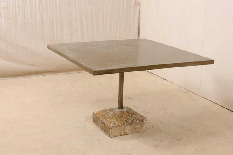 An artisan made custom 4 feet square table with an old Spanish plinth base. This table has been modernly designed in clean lines and features a patinated iron top, square in shape, with a squared iron central column which terminates into an old