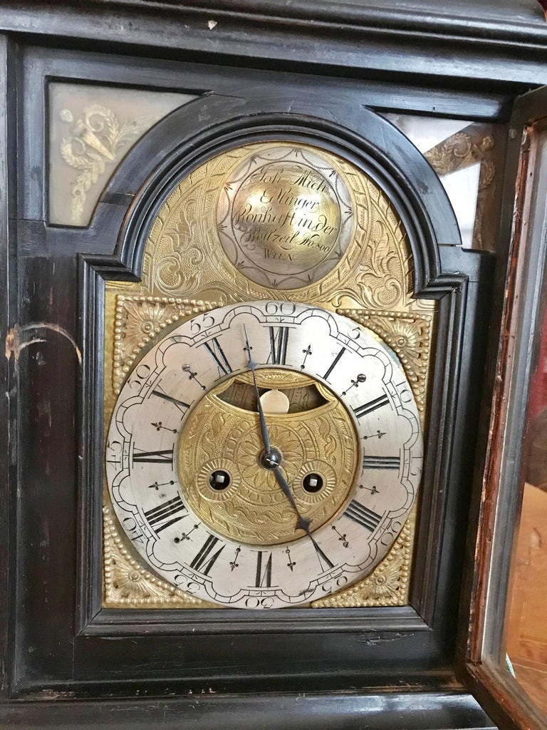 Austrian ebonized table clock ( Bracket Clock), backside engraved brass movement, spring mechanism, spindle escapement, duration 1 day, half hour strike on the bell, engraved shield arch brass dial, four-sided glazed two-door wooden case, bronze