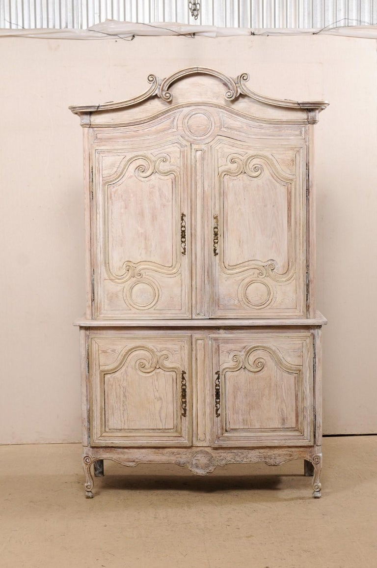 A tall French carved and painted wood storage cabinet from the early 19th century. This antique buffet à deux-corps from France features a delicately arched and molded center top pediment with curly volute accents, a pair of upper decoratively