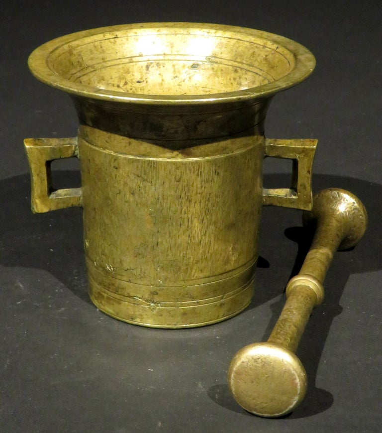 The cast body of cylindrical form rising to a flaring rim, engraved with incised ring turned detail to the exterior, interior and underside, sided by twin open handles together with what appears to be its original pestle with compressed and