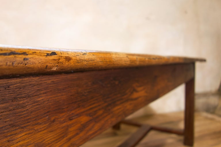 An early 19th-century oak French farmhouse refectory table. Of wide proportions, demonstrating a four plank cleated end top. Raised on square chamfered legs united by a 'H' stretcher, featuring drawers to either end of the apron. Displaying historic