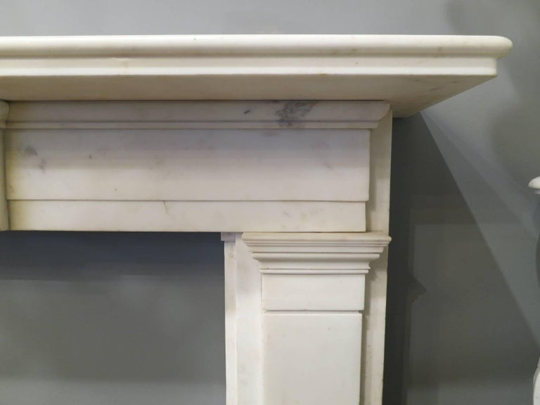 An architecturally designed Regency period fireplace in statuary white marble. The pilaster jambs with moulded and stepped capitals, supporting a stepped long frieze with plain centre tablet to centre. The mantel wide and generous with a bull nose