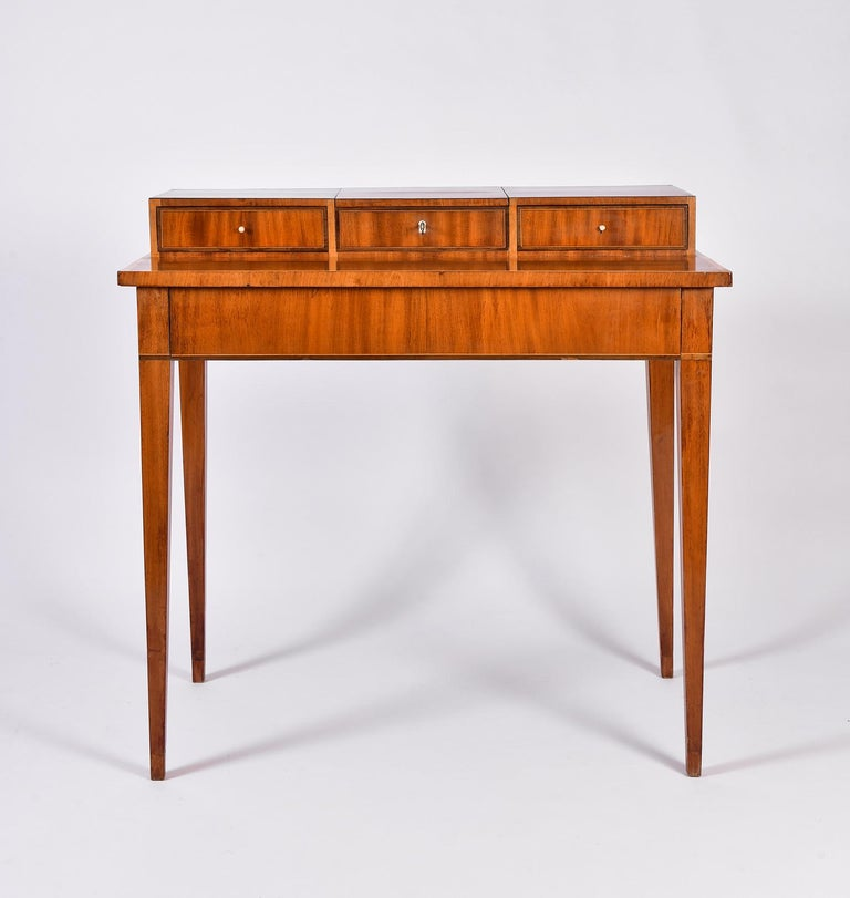 An early 19th century mahogany dressing table, the top with a long drawers above four tapered legs, topped with three drawers with bone handles, the middle dummy drawer revealing an unfolding mirror.