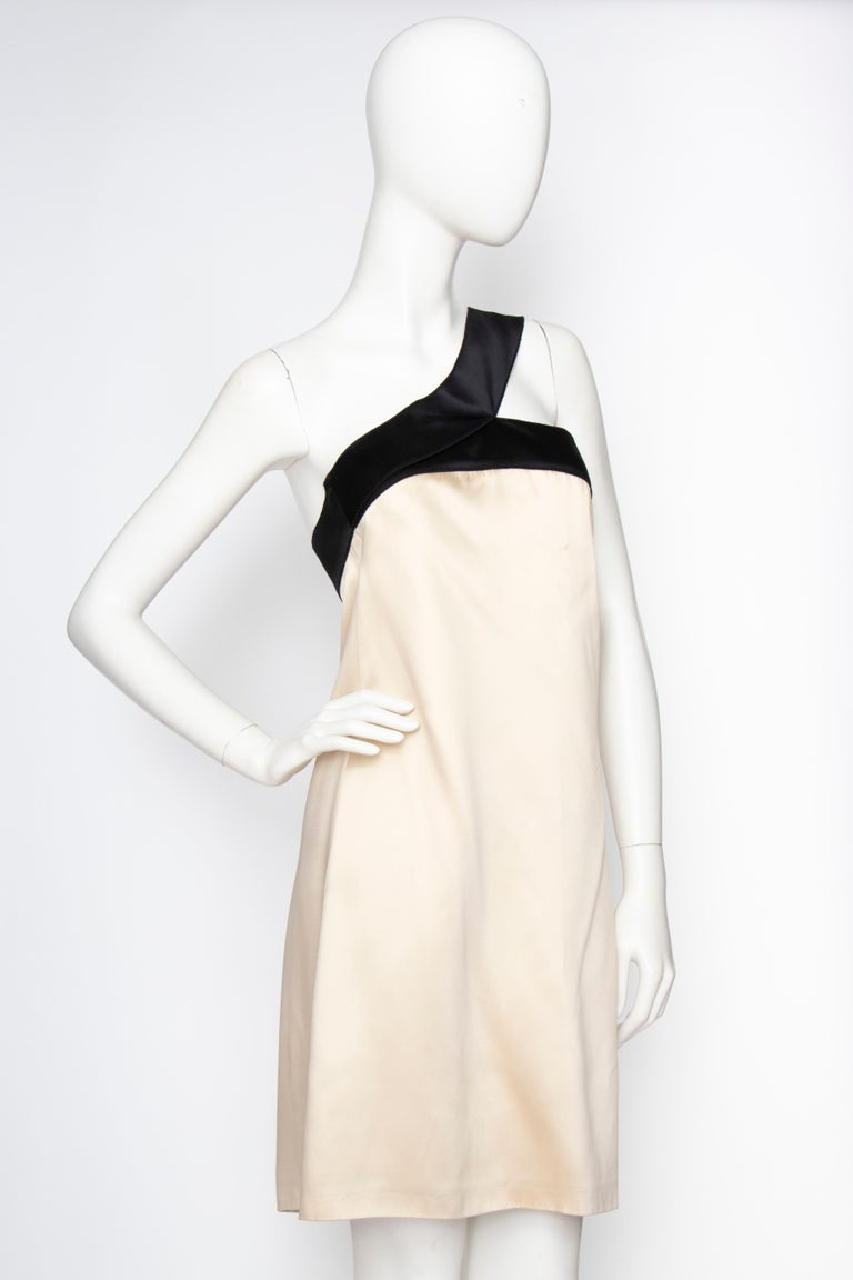 An early 2000s D&G by Dolce & Gabbana ivory satin column cocktail dress with contrasting black trim and asymmetrical shoulder strap. The dress is lined in silk and has invisible side pockets.   The size of the dress corresponds to a modern size