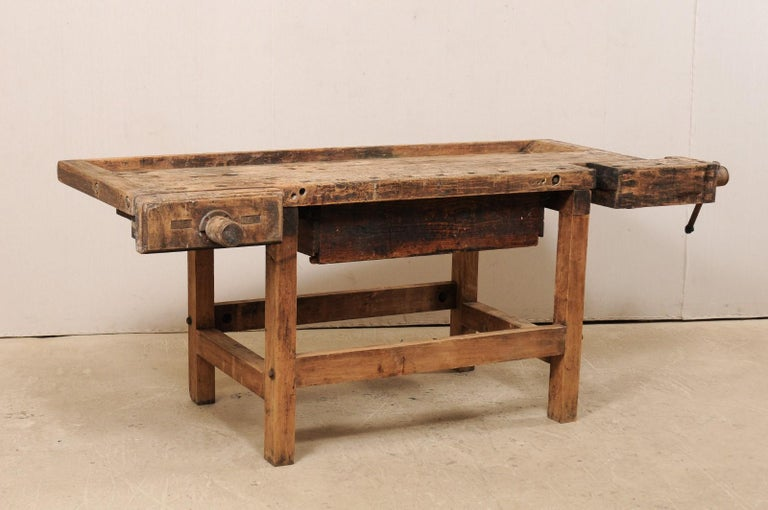An American work bench table with large drawer from the early 20th century. This antique workbench from Bethlehem, Pennsylvania (as hand-marked at underside) has a thick, rectangular-shaped top with raised lip around all sides, large adjustable