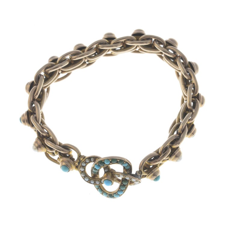 Of openwork design, the interlocking turquoise and split pearl clover, to the expanding bracelet. Length 14 to 19cms. Weight 19.3gms.