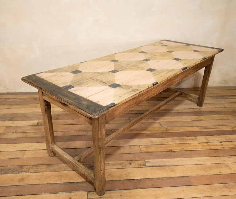 A charming early 20th century French painted refectory table. Raised on four chamfered legs, united by stretchers - demonstrating drawers to each end of the apron. The table displays a sunbleached oak base with a unique painted gridlike design to