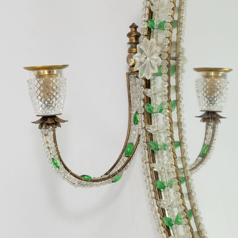 An early 20th century glass mirror, the oval plate within an ormolu frame bearing two adjustable candle arms, decorated with wire-strung clear and green glass beads and applied cut glass flower heads and sconces, English, circa 1920.