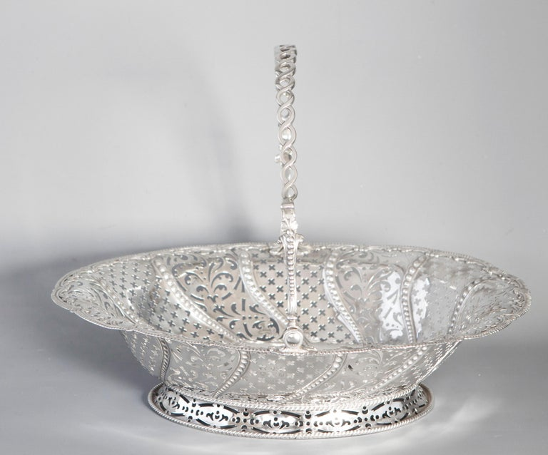 A very fine George III Silver Basket by William Plummer, London 1761. Of oval form, with pierced sides alternating in sections between cross and foliate patterns separated by tapering embossed beaded design. Shell and gadrooned boarder. Rope twist