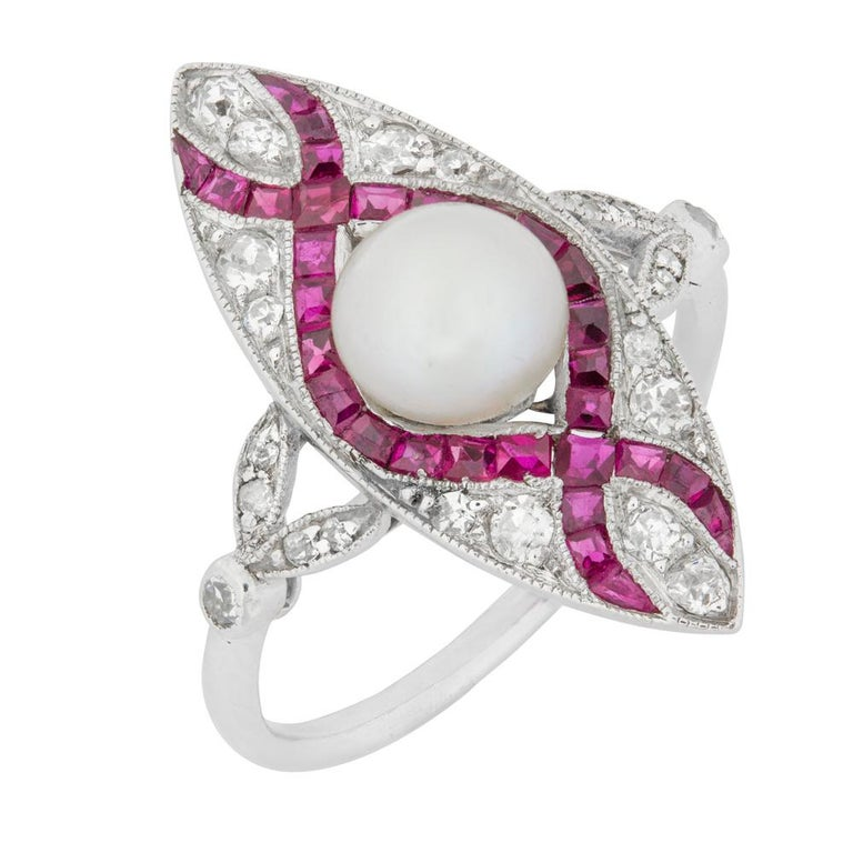 An Edwardian pearl, ruby and diamond ring, the marquise shaped ring set to the centre with a pearl measuring approximately 6mm in diameter, surrounded by calibre-cut rubies set in an extended figure-of-eight design, brilliant-cut diamonds claw set