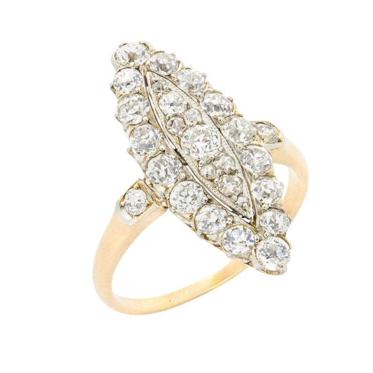 An Edwardian navette plaque old brilliant-cut diamond ring, the marquise shape centre cluster of old brilliant-cut diamonds set to a millegrain edge collet, surrounded by sixteen old brilliant-cut diamonds, all diamonds estimated to weigh a total of