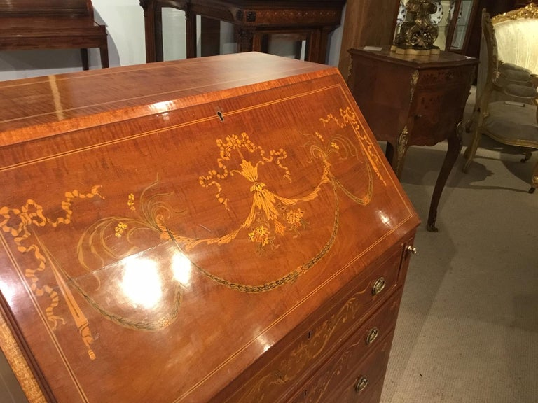 An Edwardian period mahogany inlaid antique bureau. Constructed using fiddleback mahogany and having a sloping fall front with fine marquetry and pen-work detail, opening to reveal a fitted interior with a green leather writing surface. The front