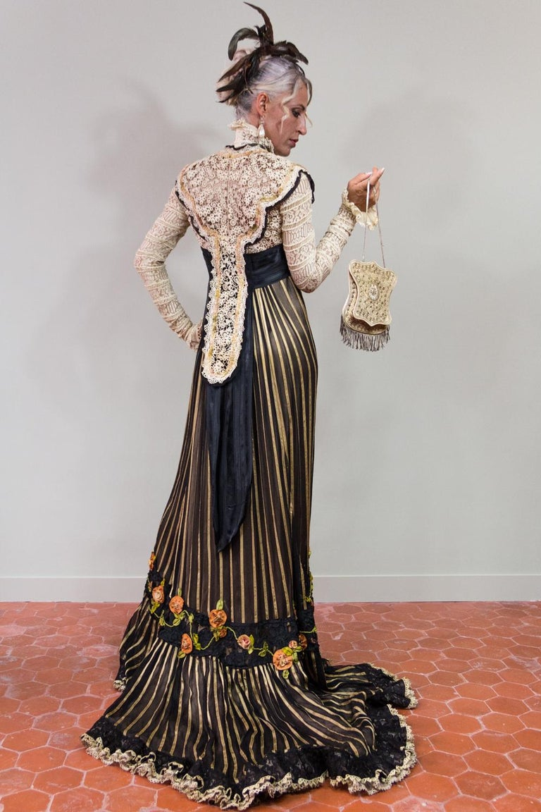 Circa 1905  France or Europe  Majestic long-tail reception or dinner dress dating from the Belle Epoque. High waist with raised officer collar, long sleeves and faux bolero open on a large black grosgrain belt ending in a point on the loins. Work of
