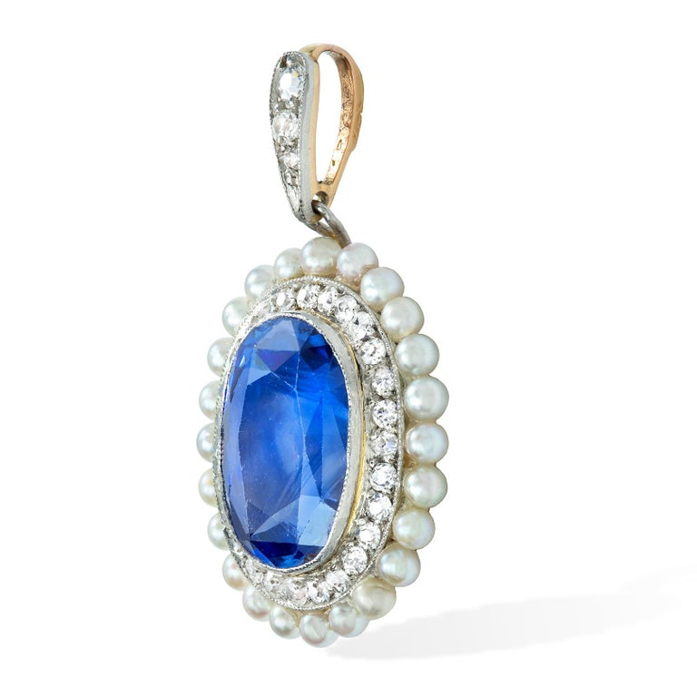 A Belle Époque sapphire diamond and pearl pendant, the oval-cut faceted sapphire weighing approximately 6.60 carats, accompanied by GCS Report 77116-67 stating to be of Sri-Lankan origin, with no indication of heat treatment, surrounded by