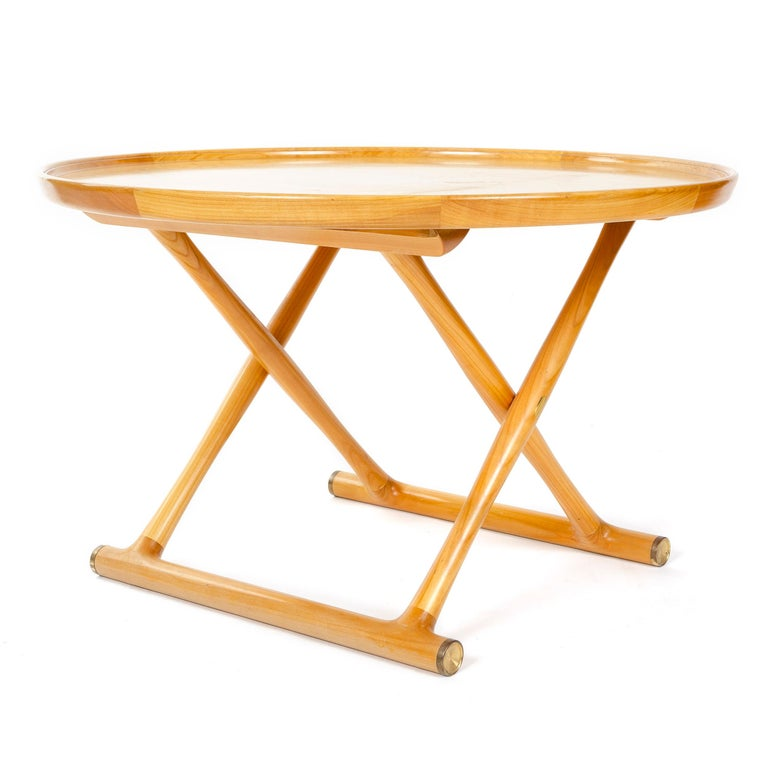 An Egyptian table designed by Mogens Lassen in light maple wood with a circular top, folding X-form legs and brass capped floor stretchers. Crafted by cabinetmaker A. J. Iversen in Denmark circa 1950s.